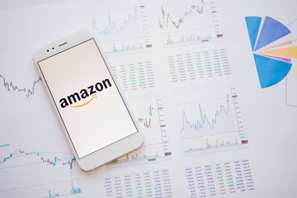 Masteradz   A white phone with Amazon's logo on the screen with a white background, the phone is on top of a white paper with research data on it