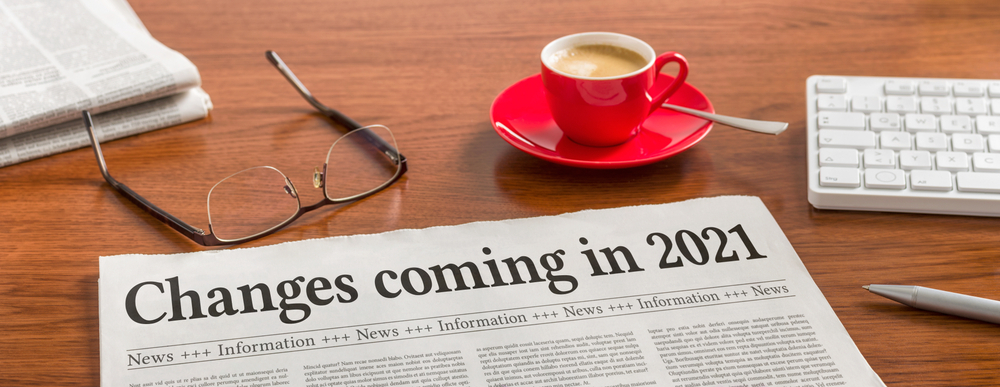 Masteradz   A newspaper with a header saying changes coming in 2021 on a wooden desk with a red coffee cup and reading glasses