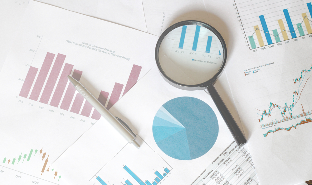 Masteradz   Papers with stock market analysis and research results in charts with a magnifier glass on top